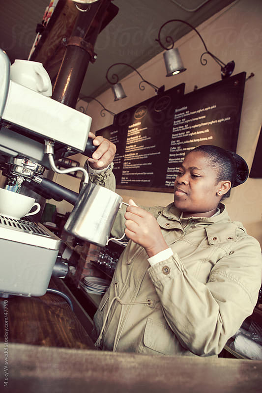 African woman making coffee in a coffee shop by Micky Wiswedel for Stocksy United