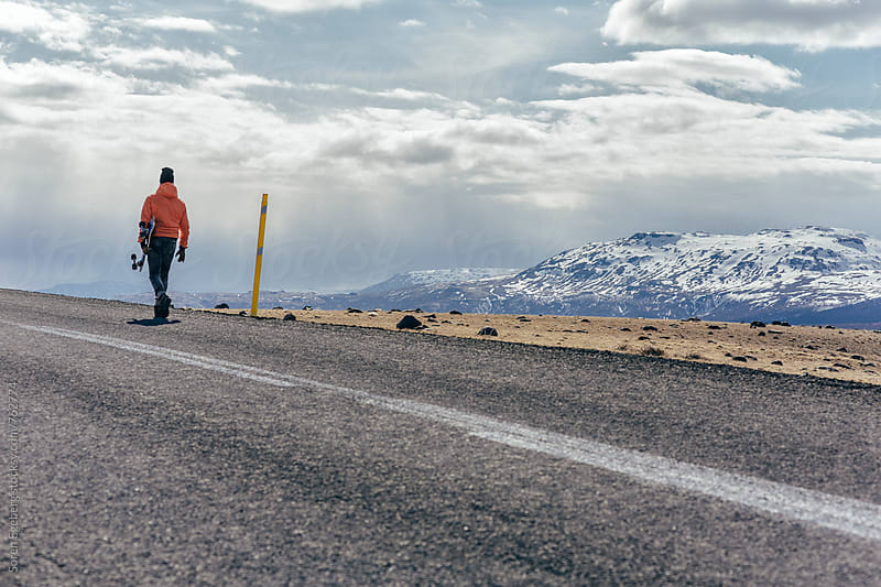 Man walking along the road with skateboard in Iceland by Søren Egeberg Photography for Stocksy United