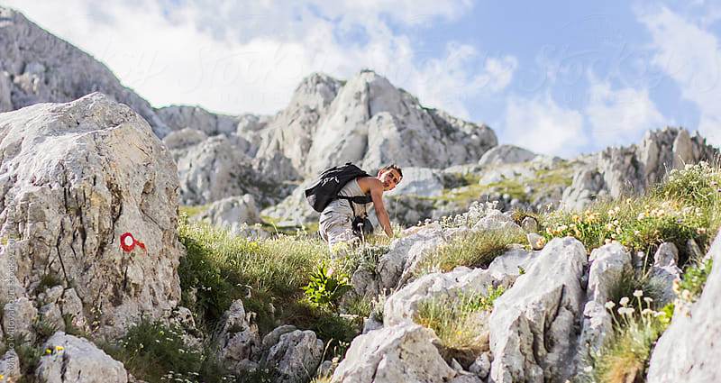 Young man climbing on the mountain, peak at the background by Marko Milovanović for Stocksy United