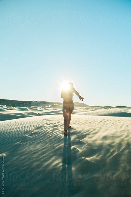 A naked woman running across sand towards the sun by Gary Parker for Stocksy United
