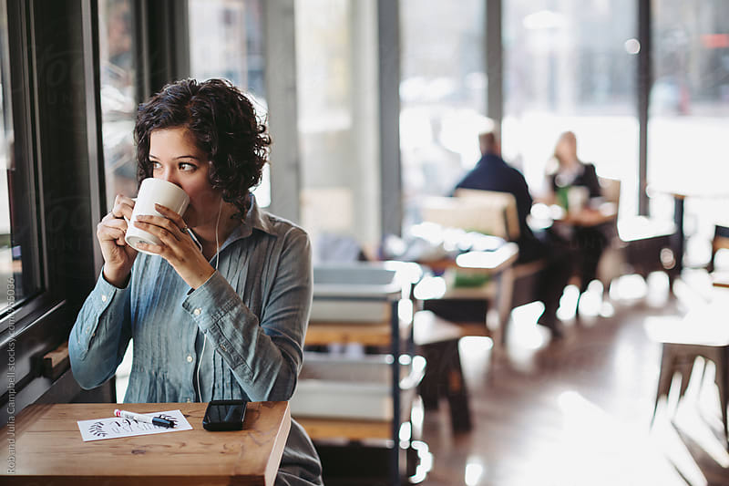 Young woman looking out window and making art in coffee shop by Rob and Julia Campbell for Stocksy United