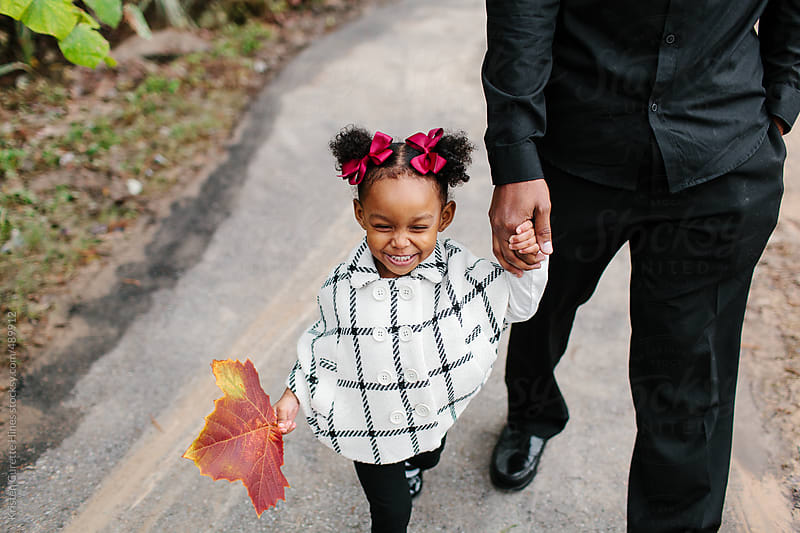 A little 2 year old girl walking in the park holding her daddy's hand by Kristen Curette Hines for Stocksy United
