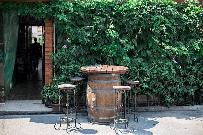 Wooden table and chairs in front of a restaurant by Maja Topcagic for Stocksy United