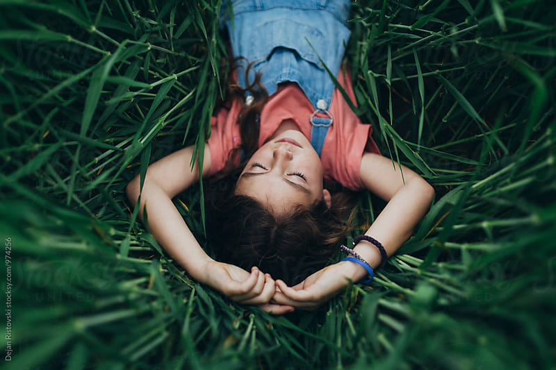 Little girl lying in the lawn. by Dejan Ristovski for Stocksy United