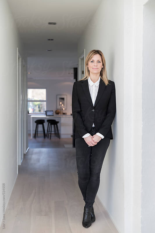 Portrait of businesswoman in black suit jacket in her stylish home by Lior + Lone for Stocksy United