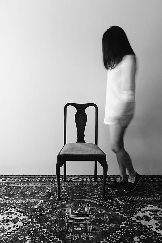 Black and white of woman and a chair, intentional movement and blur by Jacqui Miller for Stocksy United