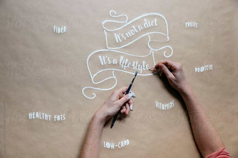 Designer's hands painting a message regarding good health on paper tablecloth by Beatrix Boros for Stocksy United