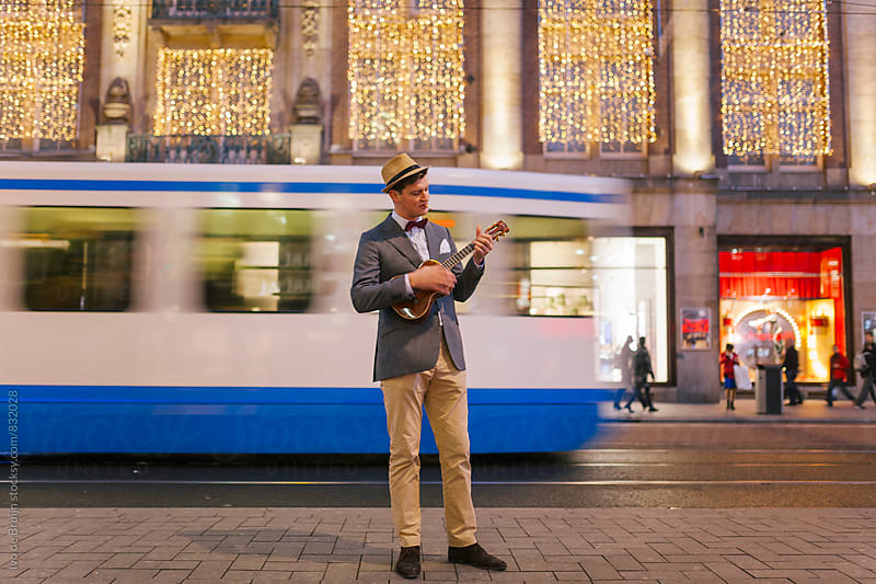 Young man smoking in a classic suit playing a ukelele, in a busy street by Ivo de Bruijn for Stocksy United