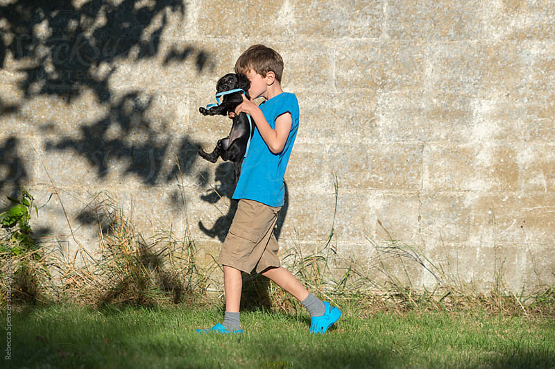 Puppy is carried by his child owner by Rebecca Spencer for Stocksy United