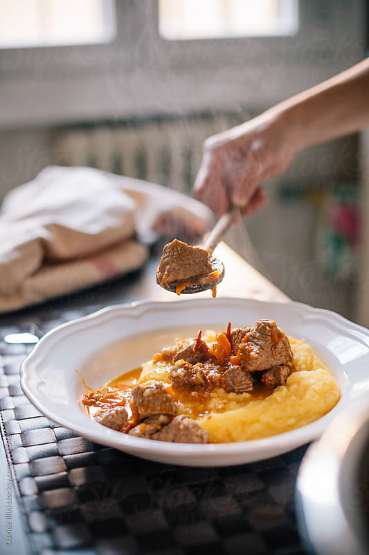 Serving beef stew with polenta by Davide Illini for Stocksy United