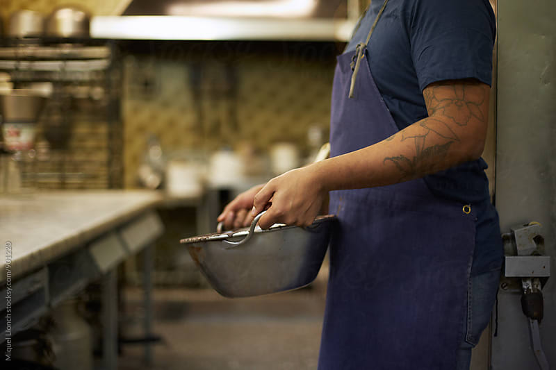 Close up of a food professional with a bowl in the kitchen by Miquel Llonch for Stocksy United