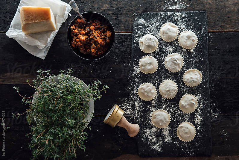 Food: Homemade Ravioli with vegetable filling on slate with cheese and herbs by Ina Peters for Stocksy United