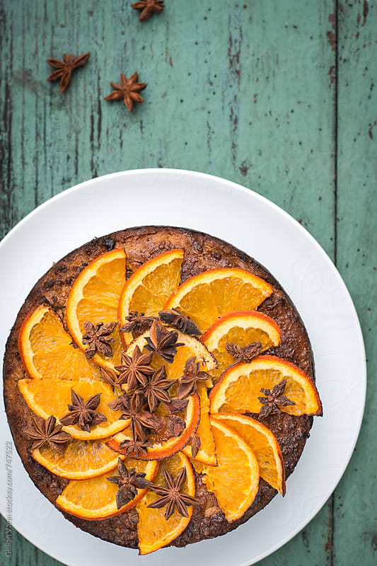 orange and almond cake, with star anise, on a wooden background by Gillian Vann for Stocksy United