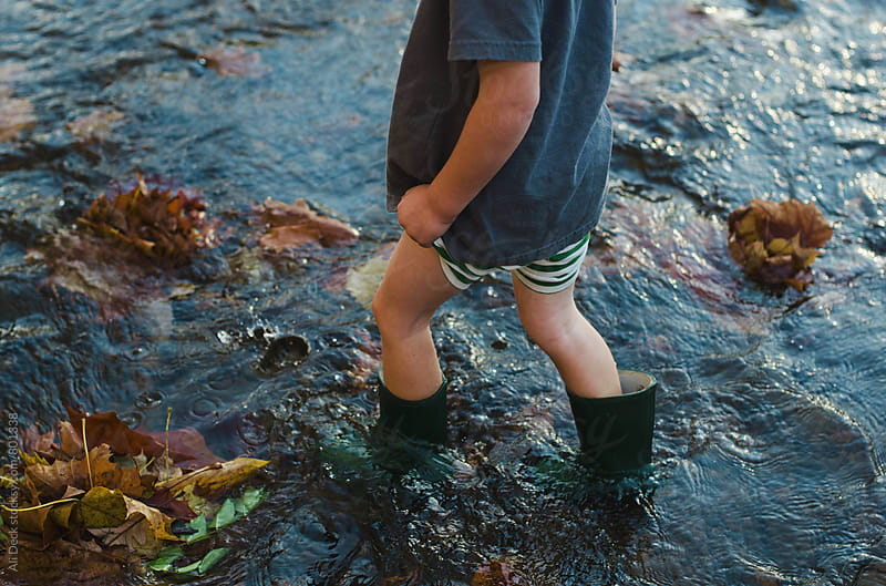 Boy in Boots in a Creek by Ali Deck for Stocksy United