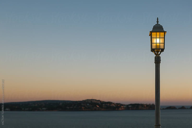 Street Lamp at Dawn with the Mediterranean Sea at Background by VICTOR TORRES for Stocksy United