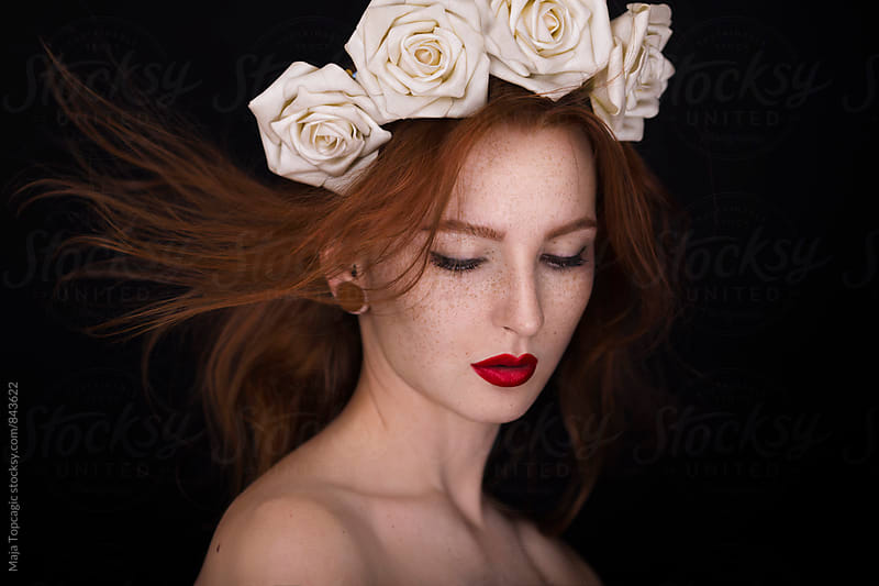 Portrait of a beautiful redhead with freckles in studio by Maja Topcagic for Stocksy United