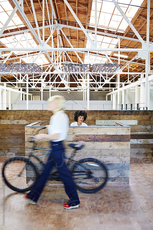 Millennial businesswoman walking with bike at office by Trinette Reed for Stocksy United