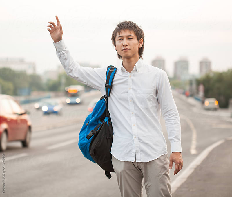 Young Man Catching a Cab by Mosuno for Stocksy United