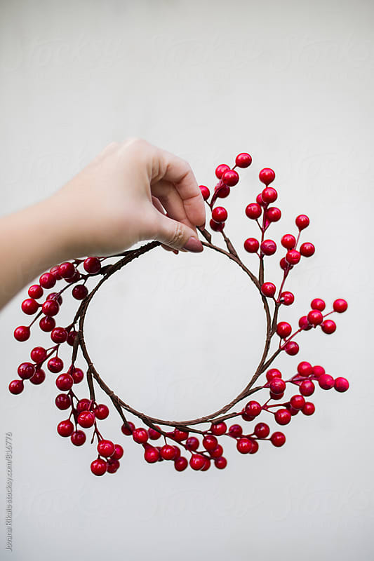 Young woman holding Christmas wreath by Jovana Rikalo for Stocksy United