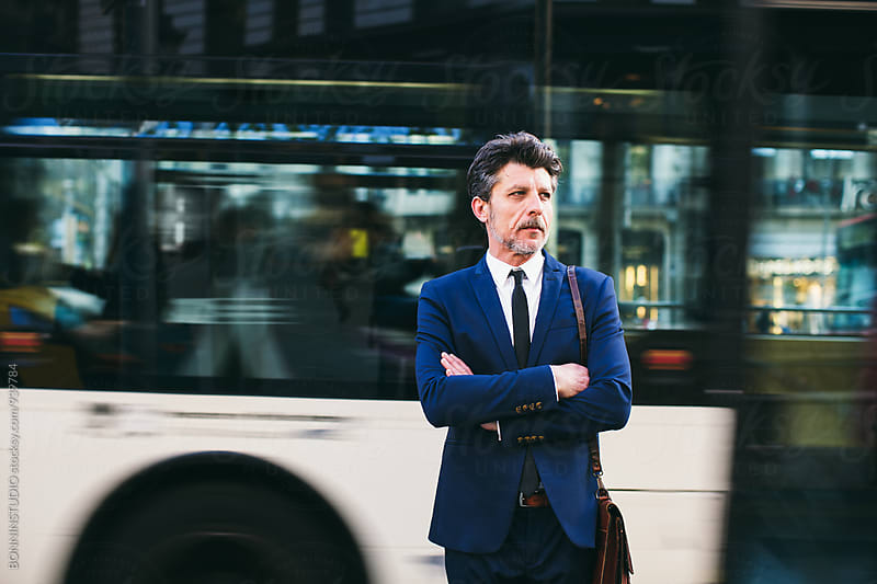 Mature businessman standing in front of the bus. by BONNINSTUDIO for Stocksy United