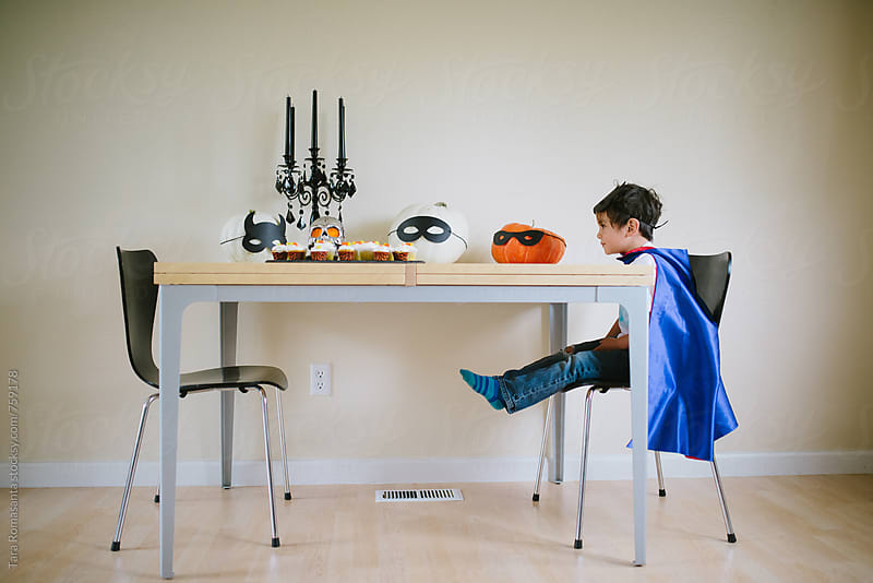 young child in super hero cape sits at table decorated for Halloween party by Tara Romasanta for Stocksy United