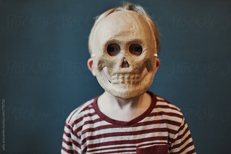 Child wearing a skull mask by sally anscombe for Stocksy United