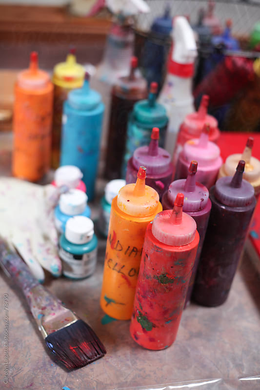 Bottles of paint and supplies in an artist's studio by Carolyn Lagattuta for Stocksy United