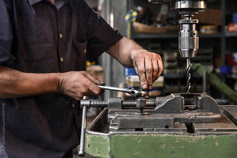 Mature craftsman drilling component in workshop by Bisual Studio for Stocksy United