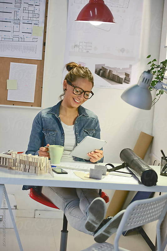 Young architect woman taking a coffee and working with digital tablet in office. by BONNINSTUDIO for Stocksy United