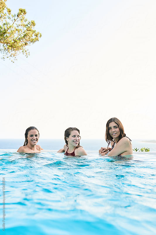 Three girlfriends in pool by Guille Faingold for Stocksy United