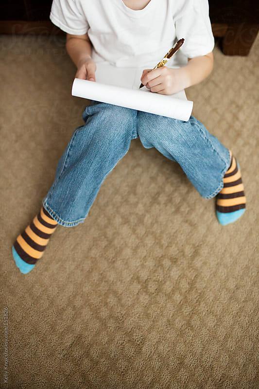 boy works on homework by Kelly Knox for Stocksy United