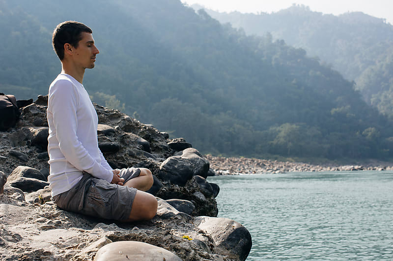 Caucasian Man Meditating by the Ganges River by Mosuno for Stocksy United