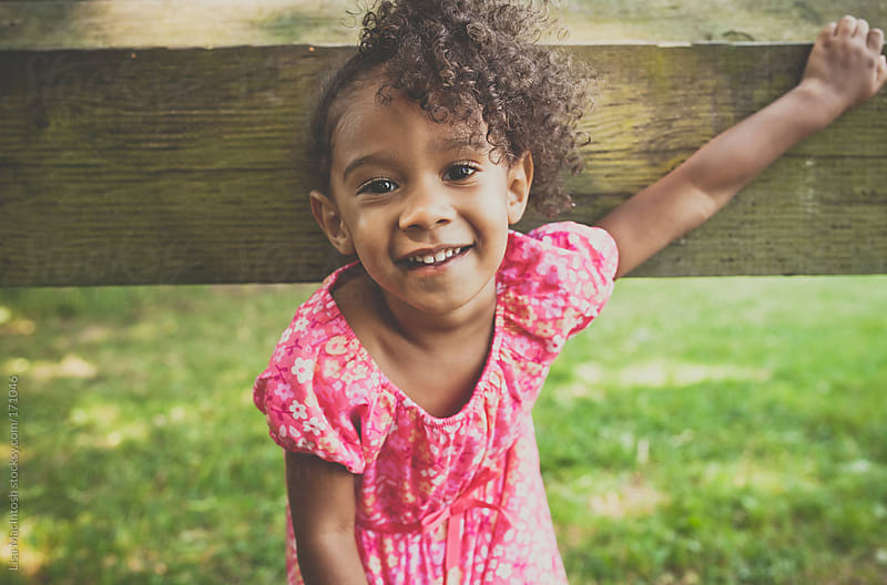 afro american girl wearing pink dress while leaning up against wooden board fence at park by Lisa MacIntosh for Stocksy United