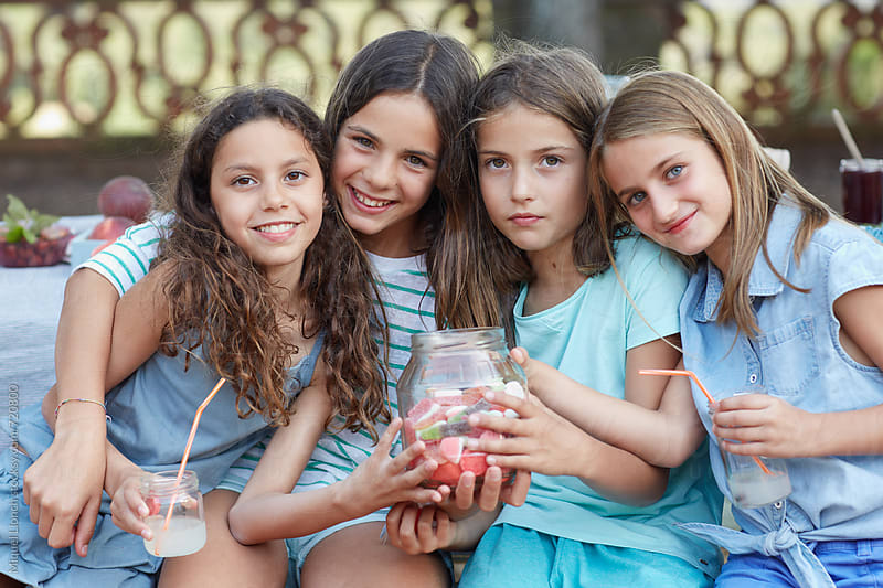 Group portrait of four young girls with lemonade drinks and a jar with candies and gummies by Miquel Llonch for Stocksy United