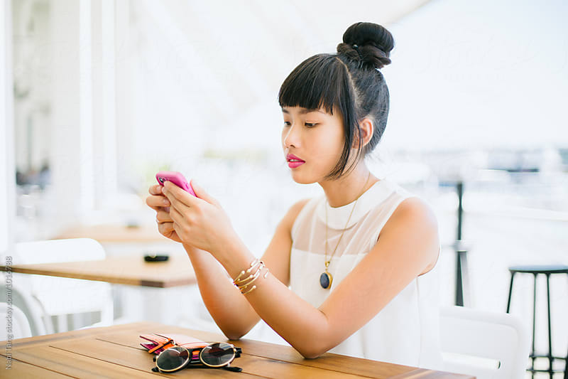 Beautiful Asian woman in white dress using mobile phone at the cafe by Nabi Tang for Stocksy United