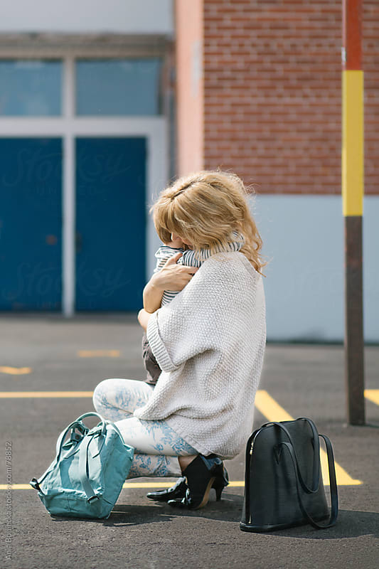 A mum and son hugging in the playground after his first day of school by Ania Boniecka for Stocksy United