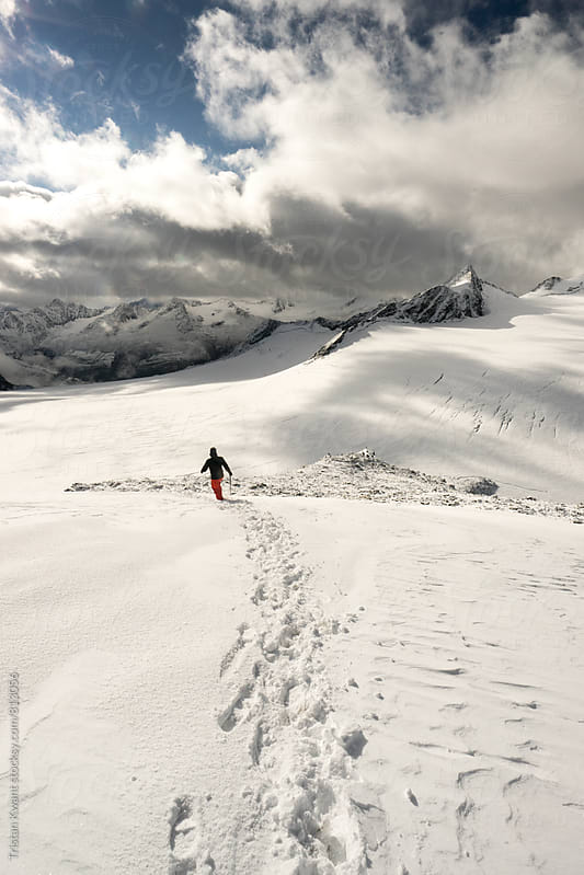 Hiking trough snow in the alps. by Tristan Kwant for Stocksy United
