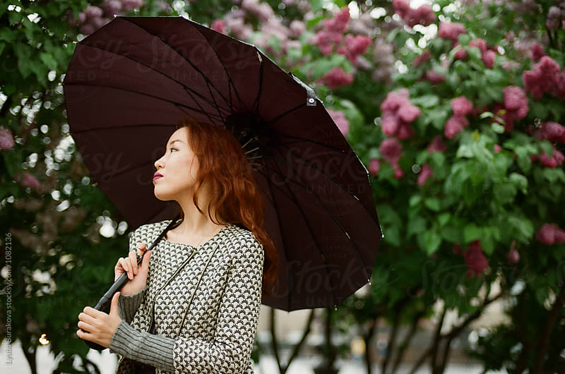 Young woman with a umbrella by Lyuba Burakova for Stocksy United