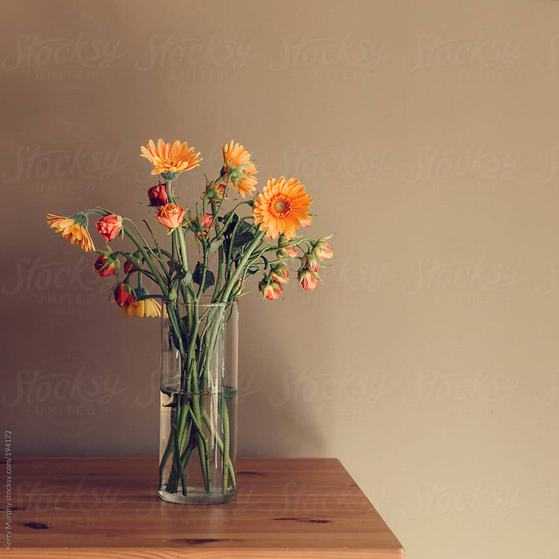 Vase of gerbera daisy and rose flowers on wooden table by Kerry Murphy for Stocksy United