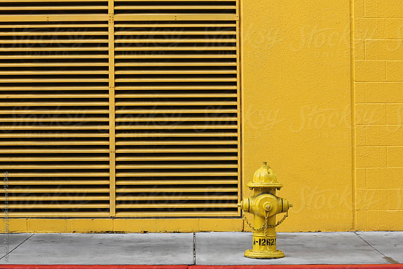 Yellow fire hydrant near yellow wall by Monica Murphy for Stocksy United