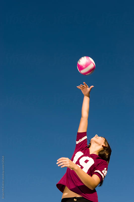 Female Volleyball Player Spiking Ball with Blue Sky by Brian McEntire for Stocksy United