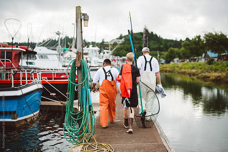 Group of fishermen walking down dock towards boat by Kate Daigneault for Stocksy United