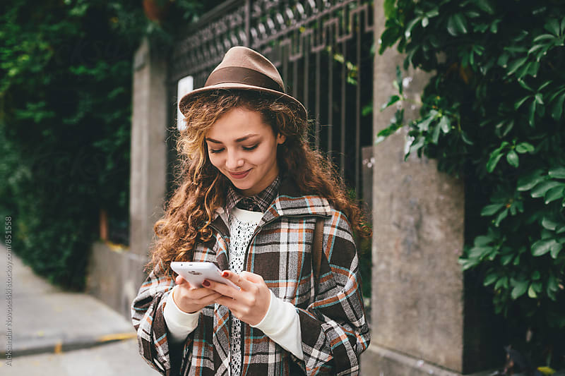 Beautiful woman with hat, smiling and texting on her smartphone by Aleksandar Novoselski for Stocksy United