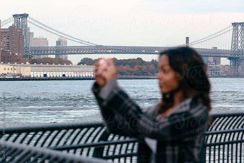Woman taking photos with mobile phone in New York by Good Vibrations Images for Stocksy United