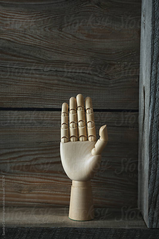 Wooden hand on shelf by Sandra Cunningham for Stocksy United