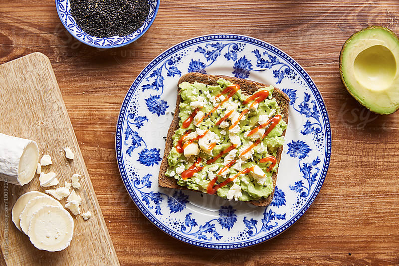 Avocado toast with mashed avocado, goat cheese and sriracha sauce by Martí Sans for Stocksy United
