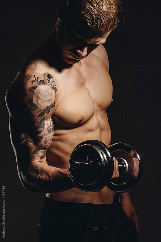male fitness man posing his muscles by Andreas Gradin for Stocksy United