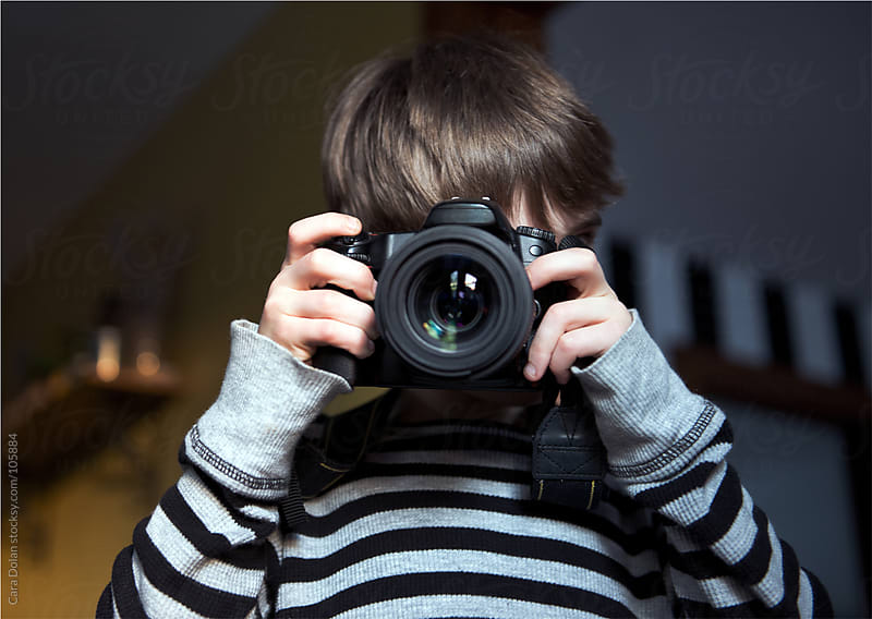 Boy takes a picture with a digital SLR camera by Cara Dolan for Stocksy United