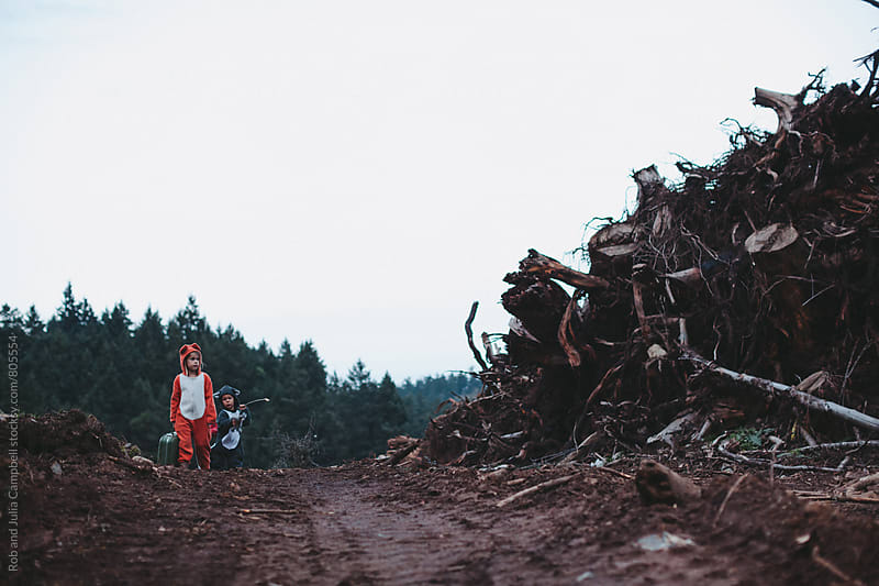 Kids dressed up like fox and raccoon walking away from destroyed home by Rob and Julia Campbell for Stocksy United