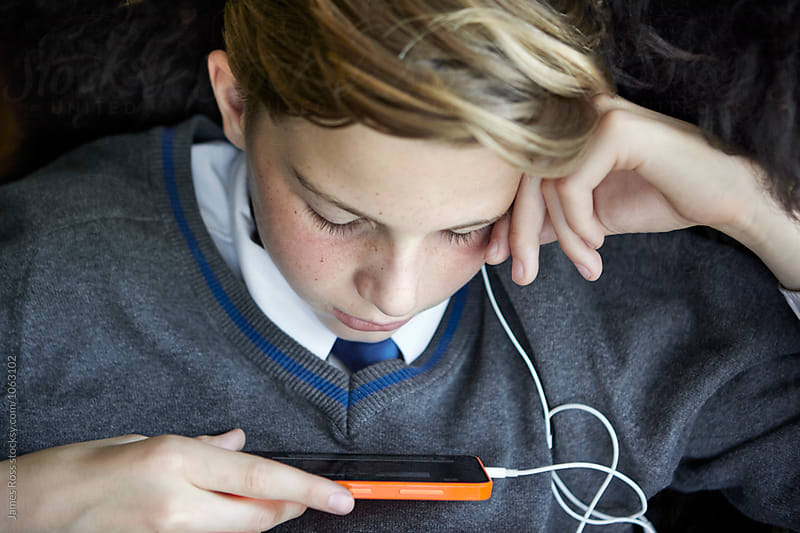 Teenage boy relaxing with his mobile phone by James Ross for Stocksy United